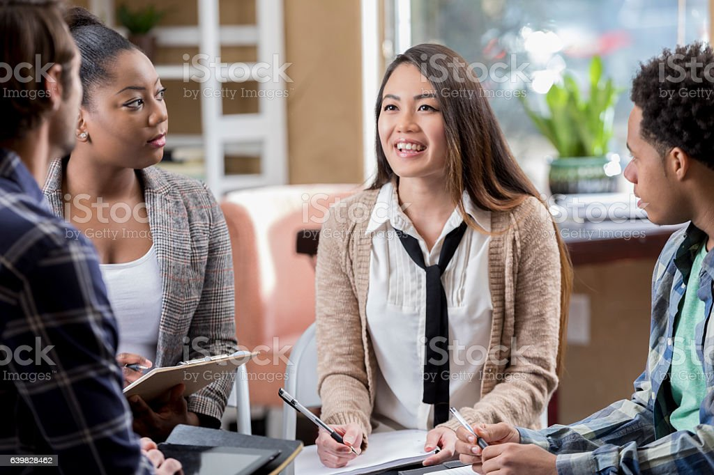 Beautiful Asian female project leader meets with group of business...