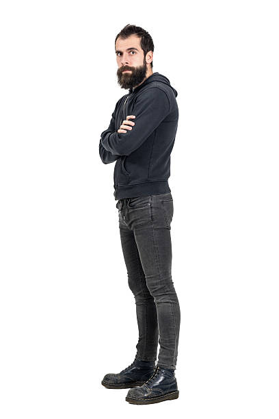 Confident punker wearing old worn boots and black hooded sweatshirt Confident serious punker wearing old worn boots and black hooded sweatshirt looking at camera. Full body length portrait isolated over white studio background men in tight jeans stock pictures, royalty-free photos & images