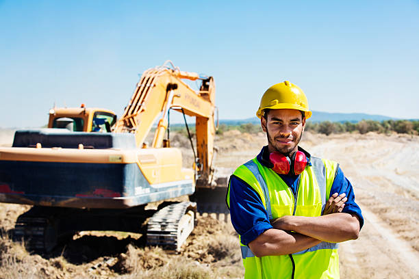 Confident quarry worker standing at site stock photo