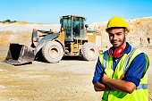 Portrait of confident quarry worker standing arms crossed at construction site