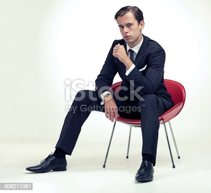 A studio portrait of a handsome young gentleman in a pinstripe suit sitting on a chair