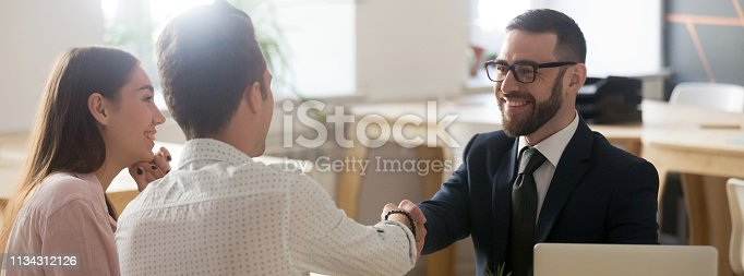 689401592 istock photo Confident realtor greeting clients young married couple in office 1134312126