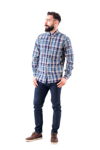 Confident relaxed bearded handsome fashion model in plaid shirt with thumbs in pockets looking away Confident relaxed bearded handsome fashion model in plaid shirt with thumbs in pockets looking away. Full body isolated on white background. plaid shirt stock pictures, royalty-free photos & images