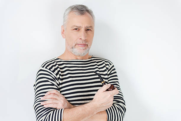 Confident sailor. Confident senior bearded man in striped clothing smoking a pipe and looking at camera while standing against white background sailor suit stock pictures, royalty-free photos & images