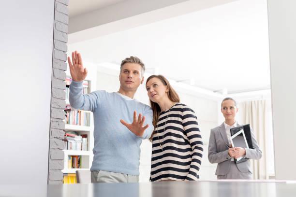 Vendedora confiada mirando a la pareja discutiendo en Apartamento - foto de stock