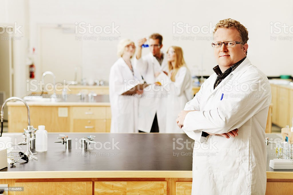 Confident scientist and his team in a laboratory royalty-free stock photo