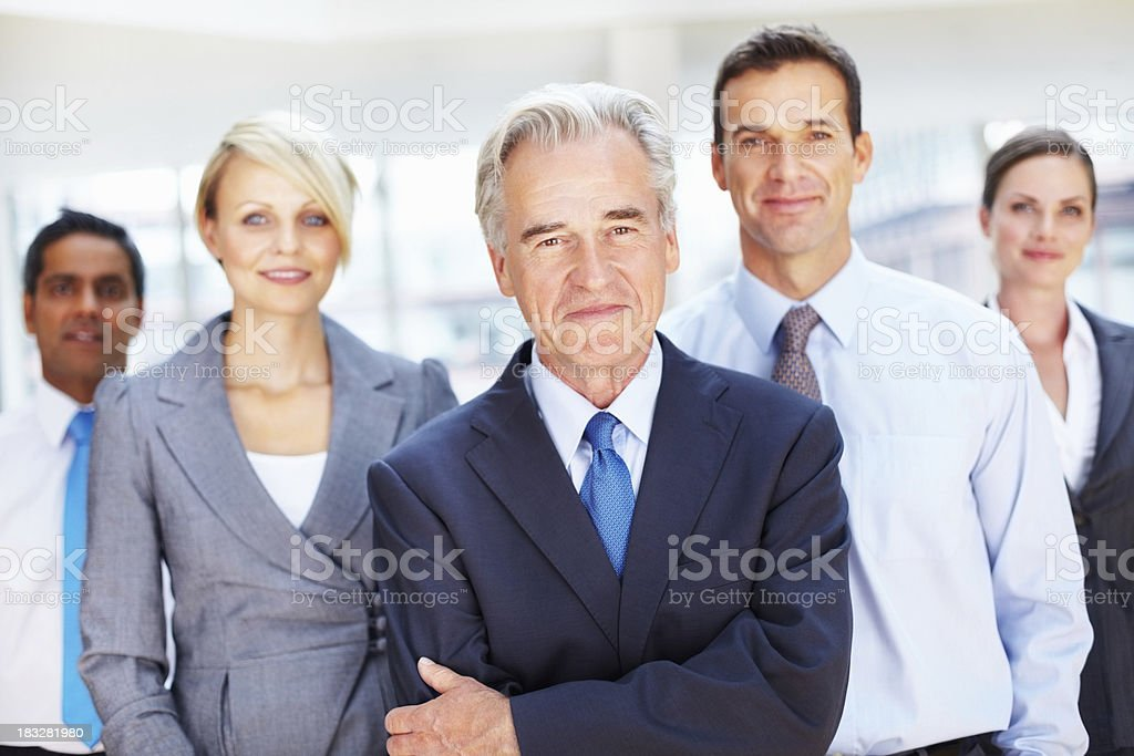 Confident senior business man with smiling colleagues in office royalty-free stock photo