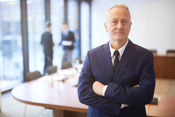 Confident Senior Businessman Posing in Conference Room Waist up portrait of successful senior businessman standing with arms crossed in conference room and looking at camera, copy space ceo stock pictures, royalty-free photos & images