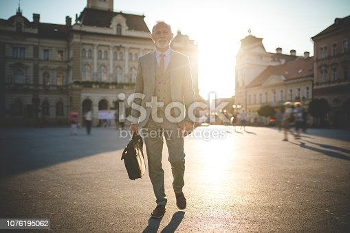 636248376istockphoto Confident senior businessman walking to the office 1076195062
