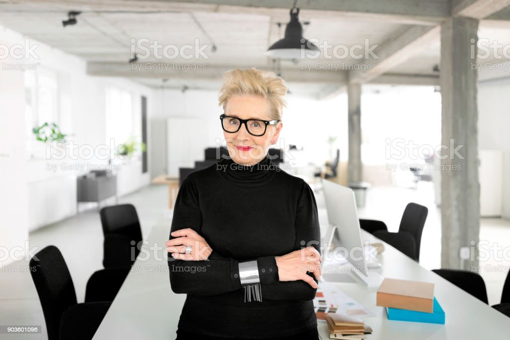 Confident senior businesswoman in the studio Portrait of senior elegant businesswoman standing in her office, smiling at the camera. 60-69 Years Stock Photo