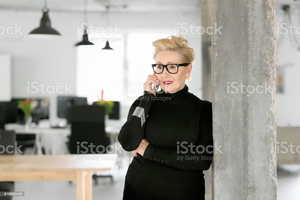 Confident senior businesswoman talking on phone in the office Portrait of elegant senior businesswoman standing in her modern office and talking on smart phone. 60-69 Years Stock Photo