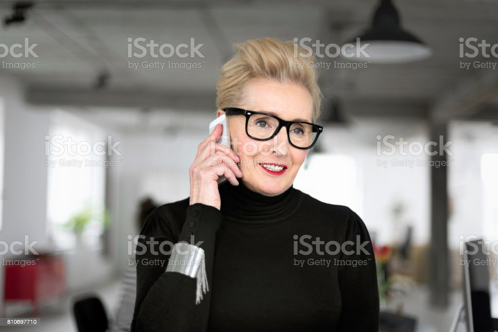 Confident senior businesswoman talking on phone in the office Portrait of elegant senior businesswoman standing in her office and talking on smart phone. Close up of face. 60-69 Years Stock Photo