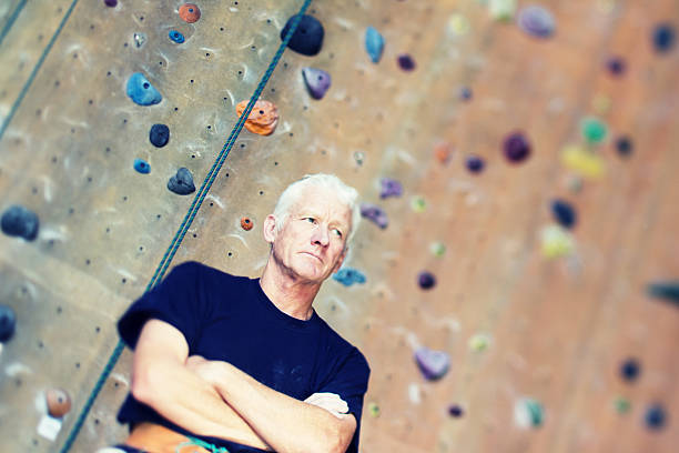 Confident Senior Climber at Rock Gym stock photo