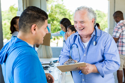 Senior Caucasian male doctor talks with mid adult Hispanic male patient at outdoor health fair. The doctor is collecting information from the patient.