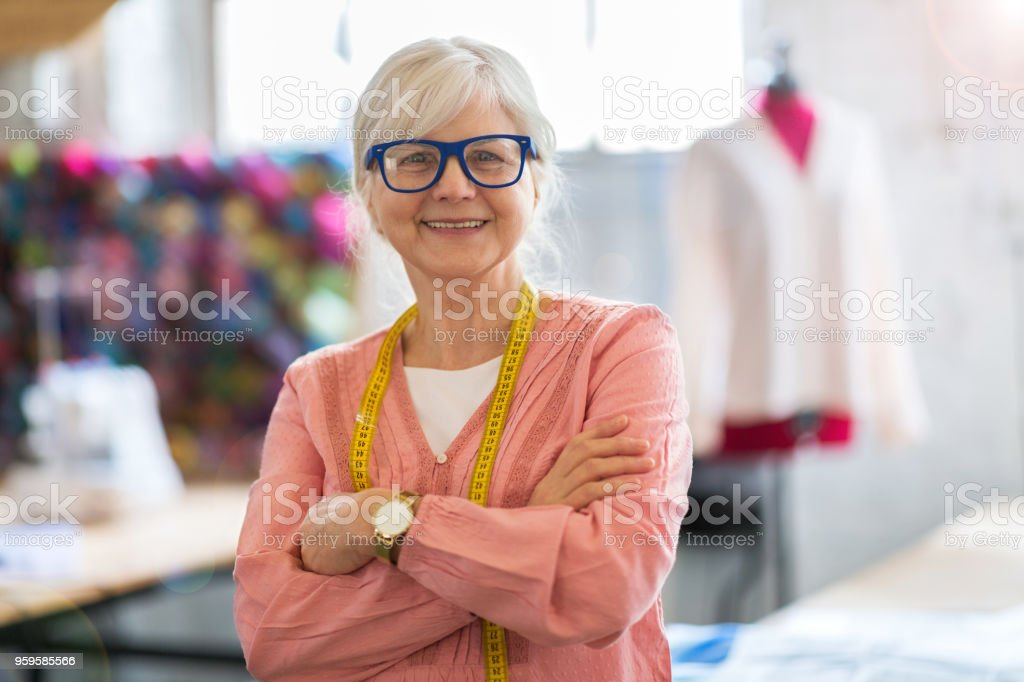 Confident senior fashion designer in her workshop stock photo
