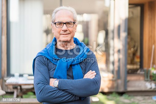 istock Confident senior man with arms crossed in backyard 541581726
