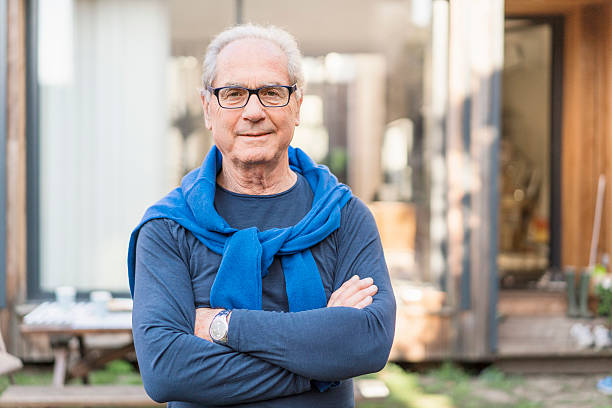 Confident senior man with arms crossed in backyard A photo of confident senior man smiling. Portrait of male is wearing casuals. He is standing arms crossed in backyard. 65 69 years stock pictures, royalty-free photos & images