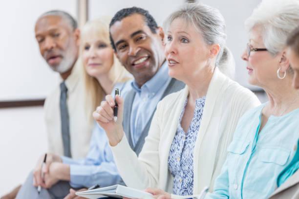 confident senior woman asks question during seminar - pensionati lavoratori foto e immagini stock