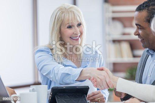487670635istockphoto Confident senior woman greets a colleague 696977670