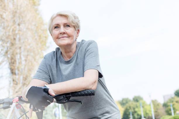 Mujer de mayor confianza apoyada en el manillar de la bicicleta en el Parque - foto de stock