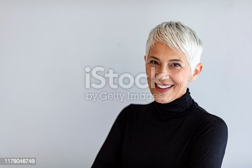 Close up portrait of beautiful older gray hair woman smiling and standing by gray wall wearing black turtleneck.