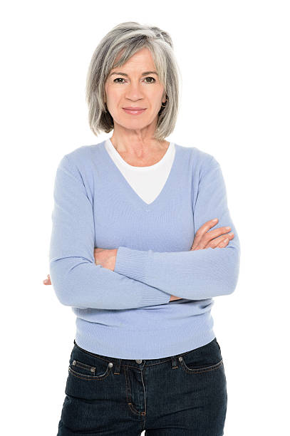 Confident Senior Woman Portrait of a confident senior woman standing with arms crossed isolated over white background. Vertical shot. 60 64 years stock pictures, royalty-free photos & images