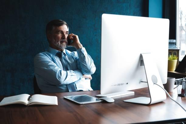 Zuversichtlich lächelnder Geschäftsmann mit einem Telefonanruf auf seinem Smartphone. – Foto