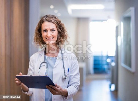 Smiling female doctor with clipboard in corridor. Portrait of confident medical professional is wearing lab coat and stethoscope. She is standing at hospital.