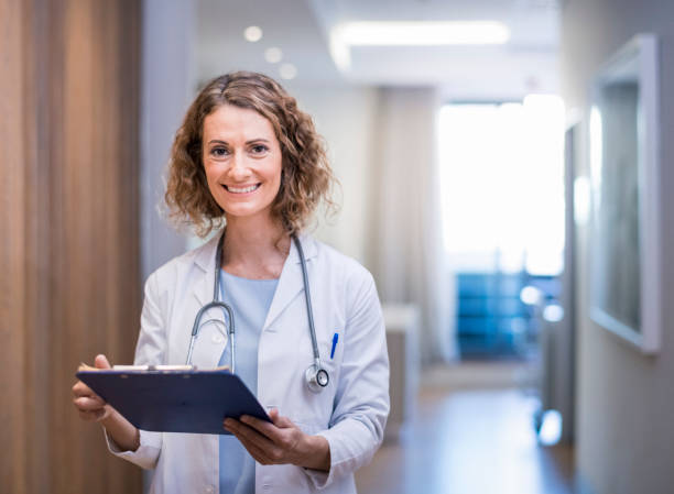 Confident smiling female doctor with clipboard Smiling female doctor with clipboard in corridor. Portrait of confident medical professional is wearing lab coat and stethoscope. She is standing at hospital. female doctor stock pictures, royalty-free photos & images