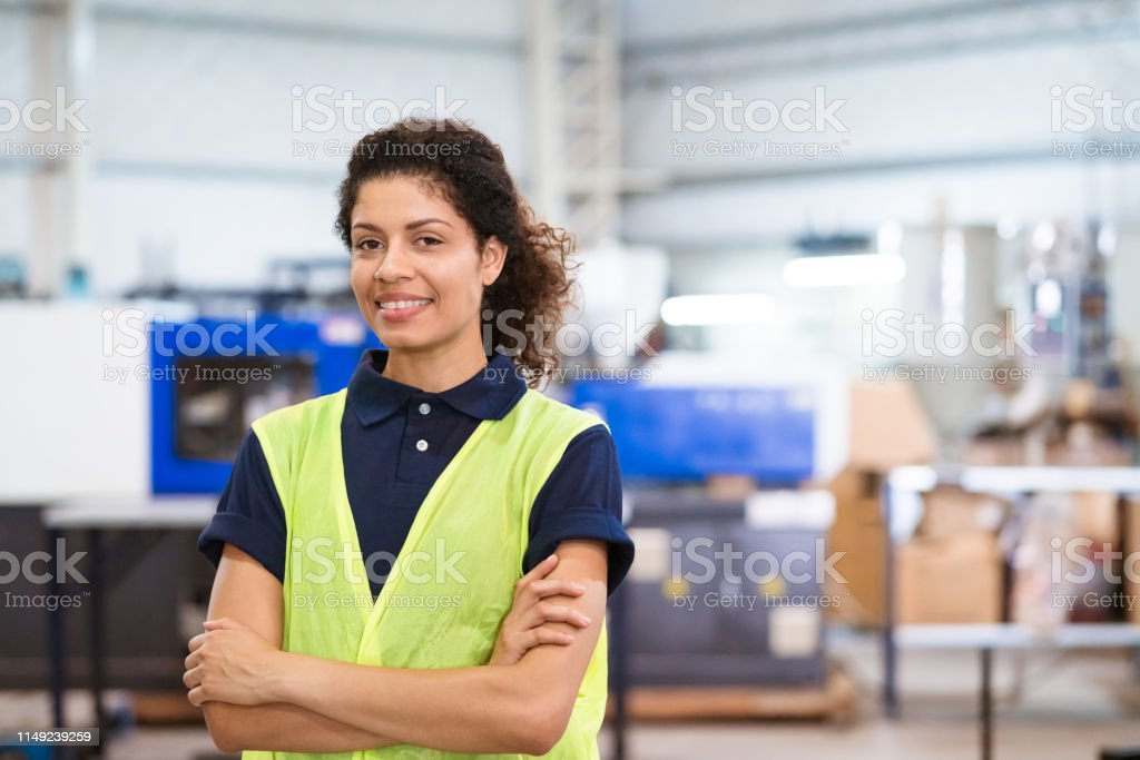 Confident smiling female trainee with arms crossed Confident smiling female engineer with arms crossed. Portrait of mid adult apprentice is in reflective clothing. She is standing in metal industry. 30-34 Years Stock Photo
