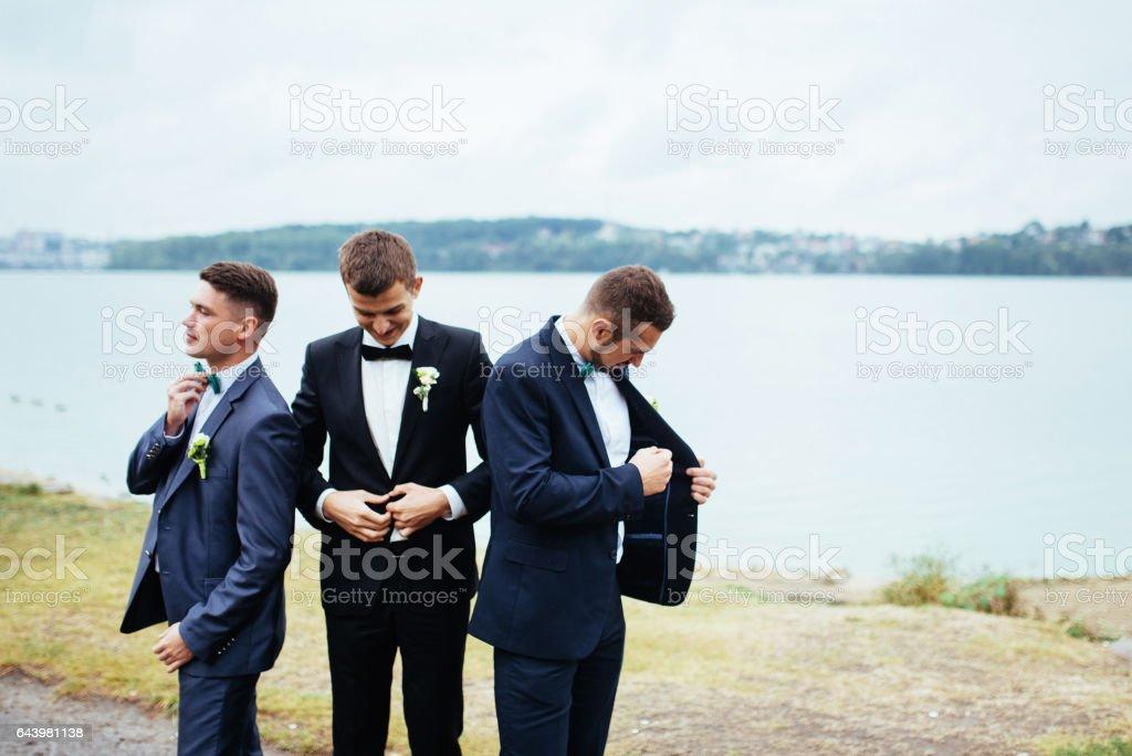 Zuversichtlich lächelnden schönen Bräutigam im schwarzen Anzug mit zwei groomsma – Foto