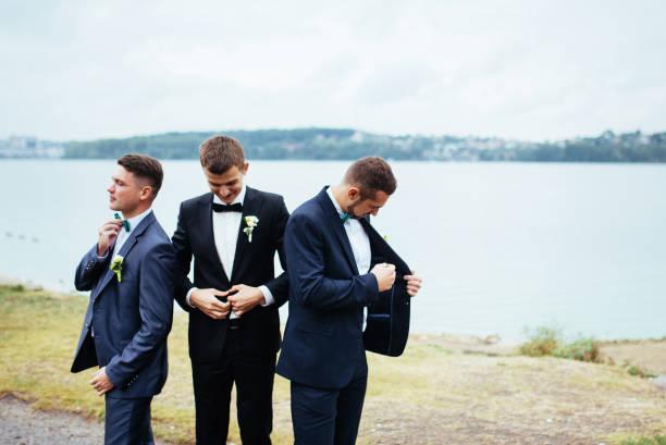 zuversichtlich lächelnden schönen bräutigam im schwarzen anzug mit zwei groomsma - hochzeitsanzug herren stock-fotos und bilder