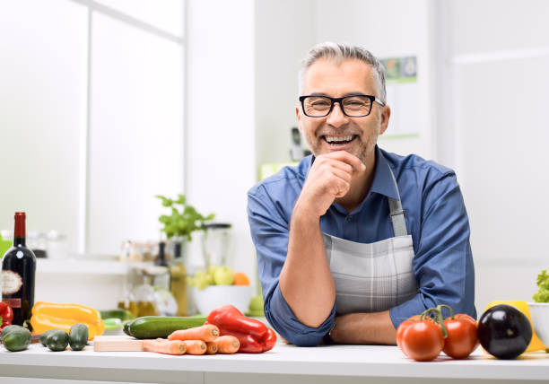 Confident smiling man posing in his kitchen Smiling man posing in the kitchen, he is preparing healthy homemade food using fresh organic vegetables only mature men stock pictures, royalty-free photos & images