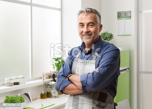 istock Confident smiling man posing in his kitchen 867929270