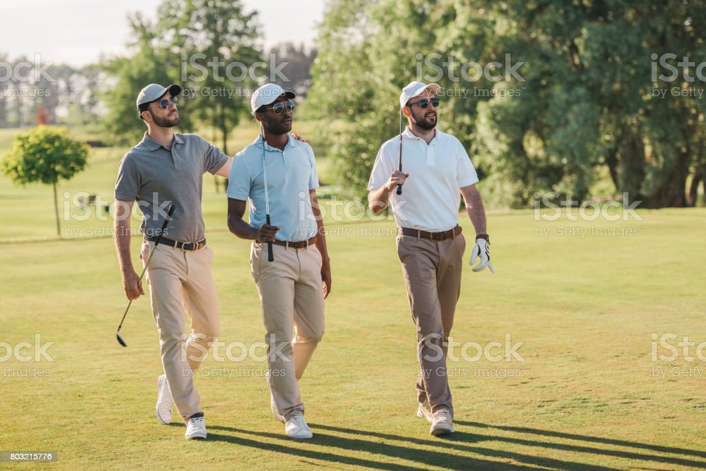 Confident smiling men in caps and sunglasses holding golf clubs and walking on lawn stock photo