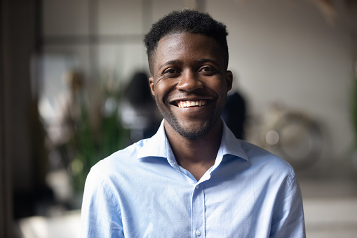 Confident smiling millennial african american businessman looking at camera in modern office, happy male professional company leader coach trainer posing alone, close up head shot business portrait