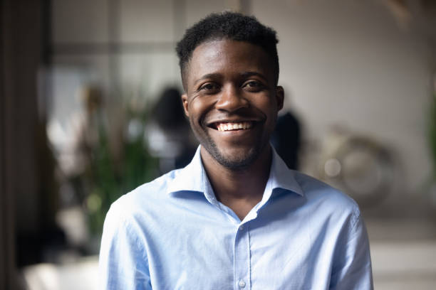 confident smiling young african businessman looking at camera in office - coinvolgimento dei dipendenti foto e immagini stock