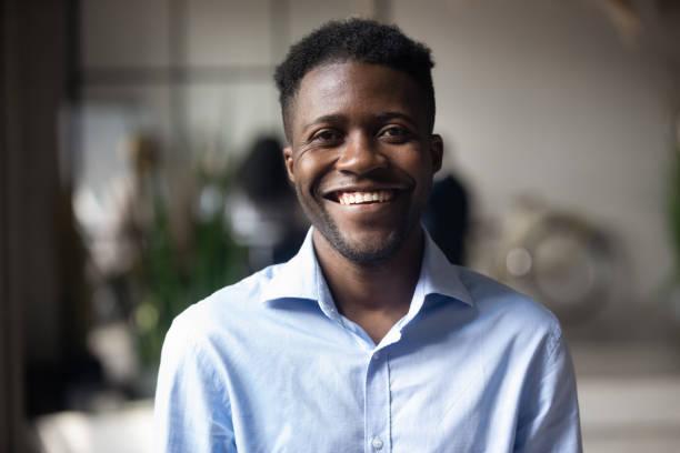 homem de negócios africano novo de sorriso de confiança que olha a câmera no escritório - man portrait - fotografias e filmes do acervo