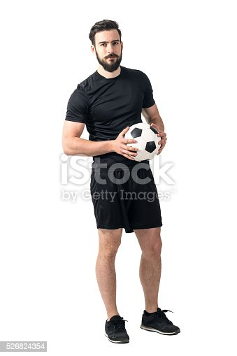 istock Confident soccer player holding ball with daring look to camera 526824354
