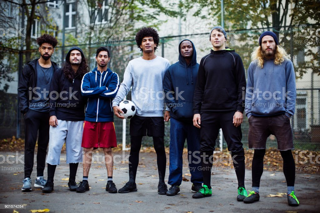 Confident soccer players standing against fence stock photo