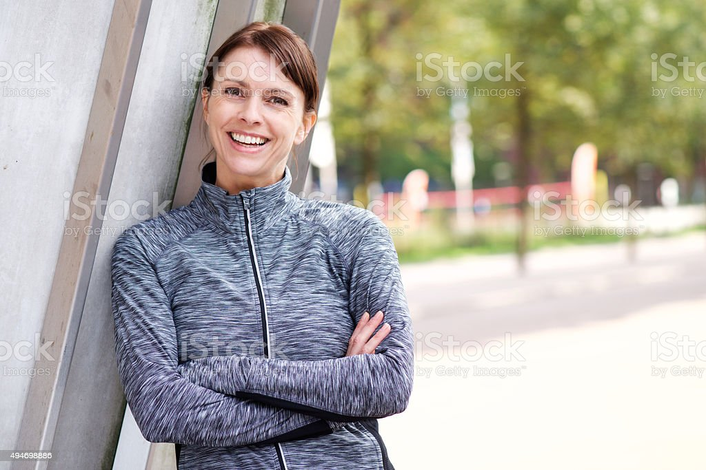 Confident sports woman smiling outdoors stock photo