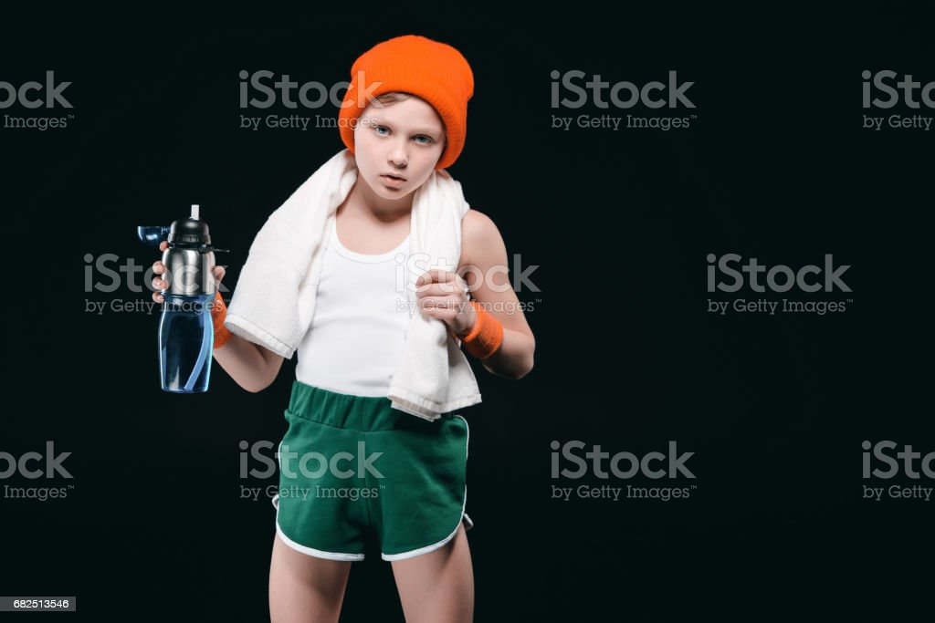 Confident sporty boy with towel on neck holding sports bottle with water isolated on black royalty-free stock photo
