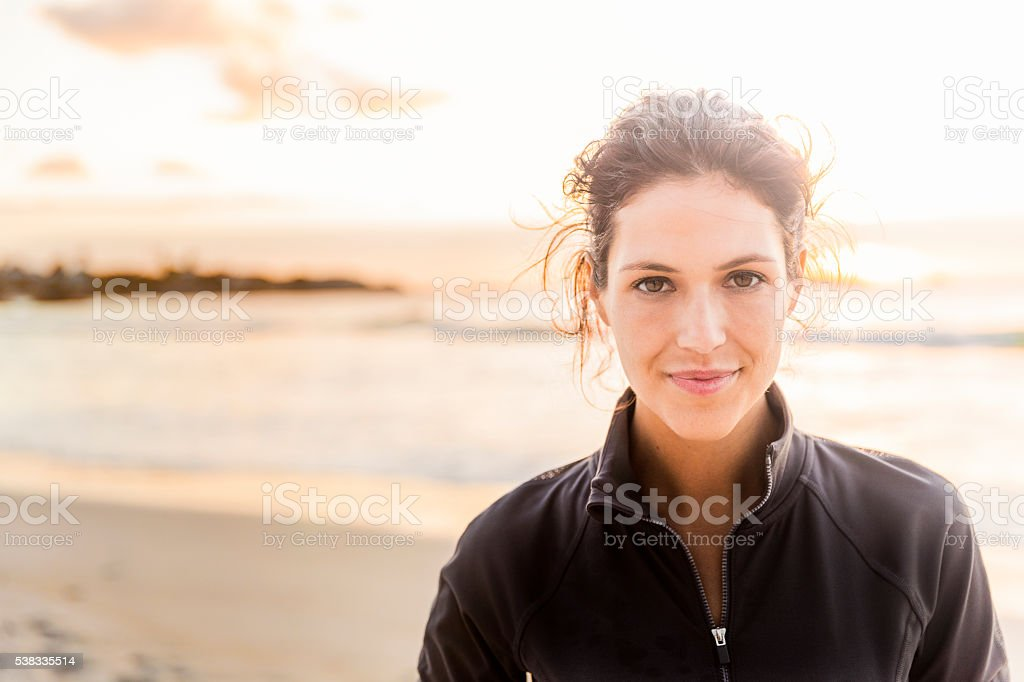 Confident sporty woman at beach stock photo