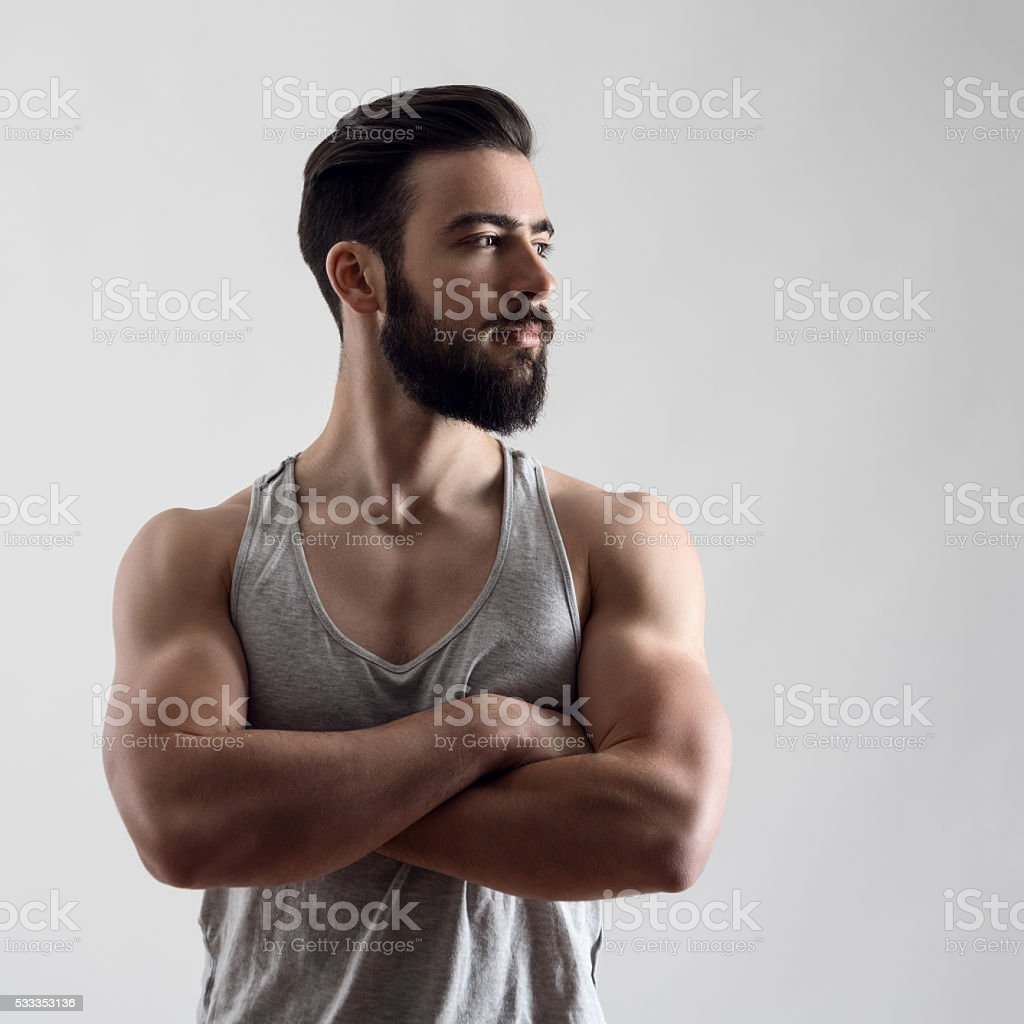 Confident strong handsome bearded athlete with crossed arms looking away stock photo