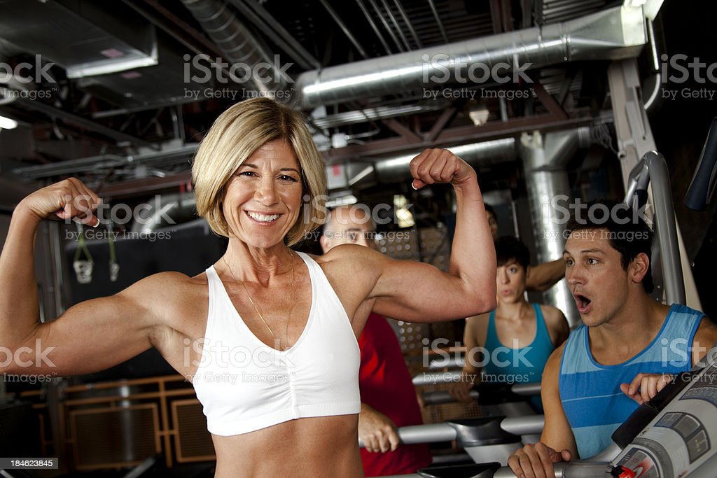 Confident strong smiling woman at  gym focus on biceps royalty-free stock photo
