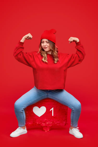 confident strong woman in beanie sitting on like sign - vr red background imagens e fotografias de stock