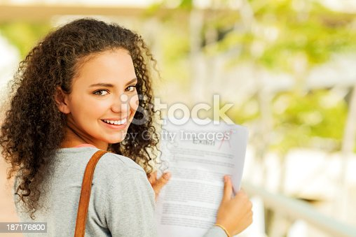 istock Confident Student Holding Exam Result With A+ Grade On Campus 187176800