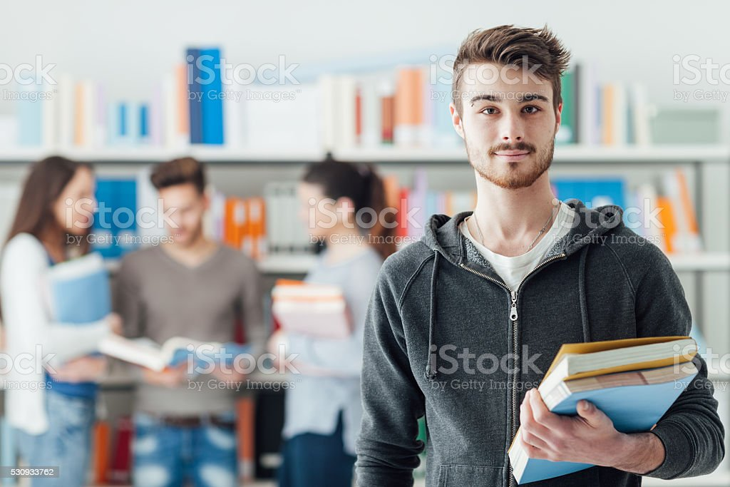 Confident student posing in the library stock photo