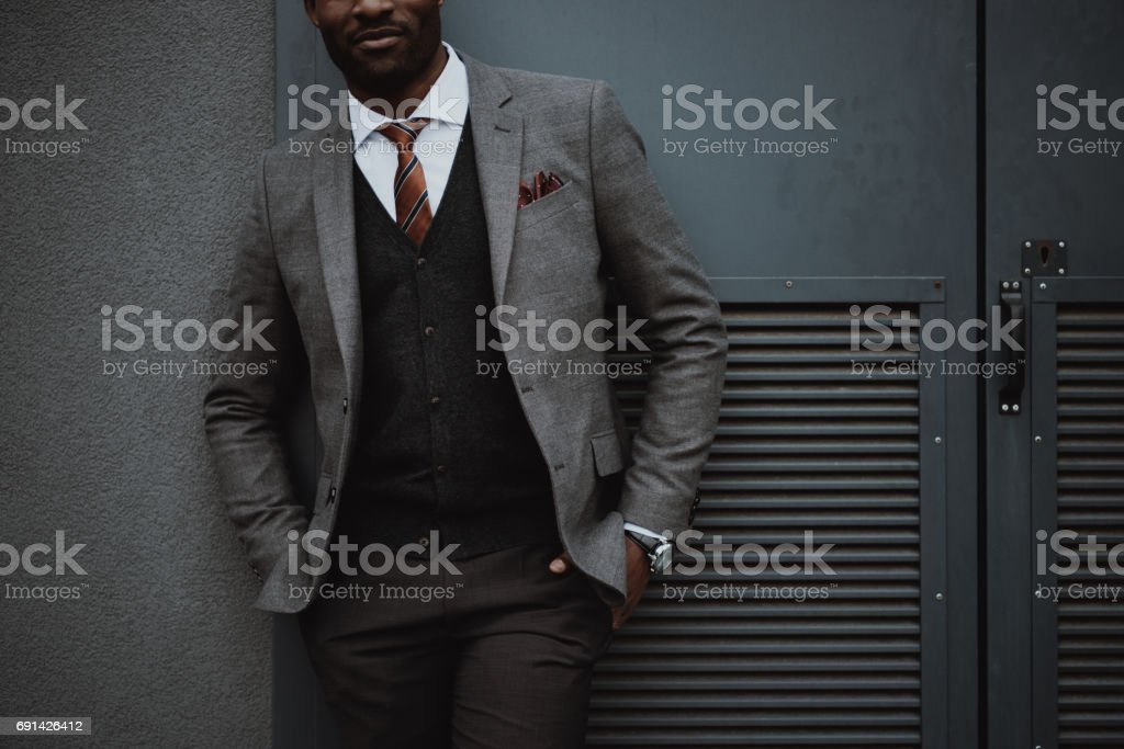 confident stylish african american businessman posing outdoors at wall stock photo