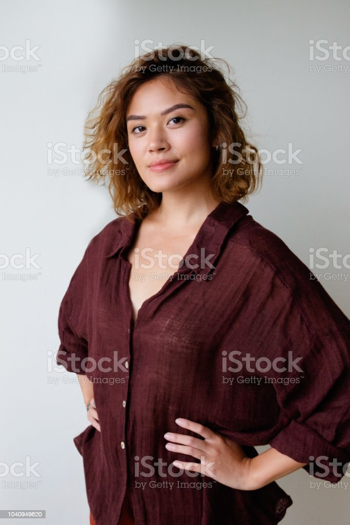 Confident stylish Asian girl posing in oversized shirt stock photo